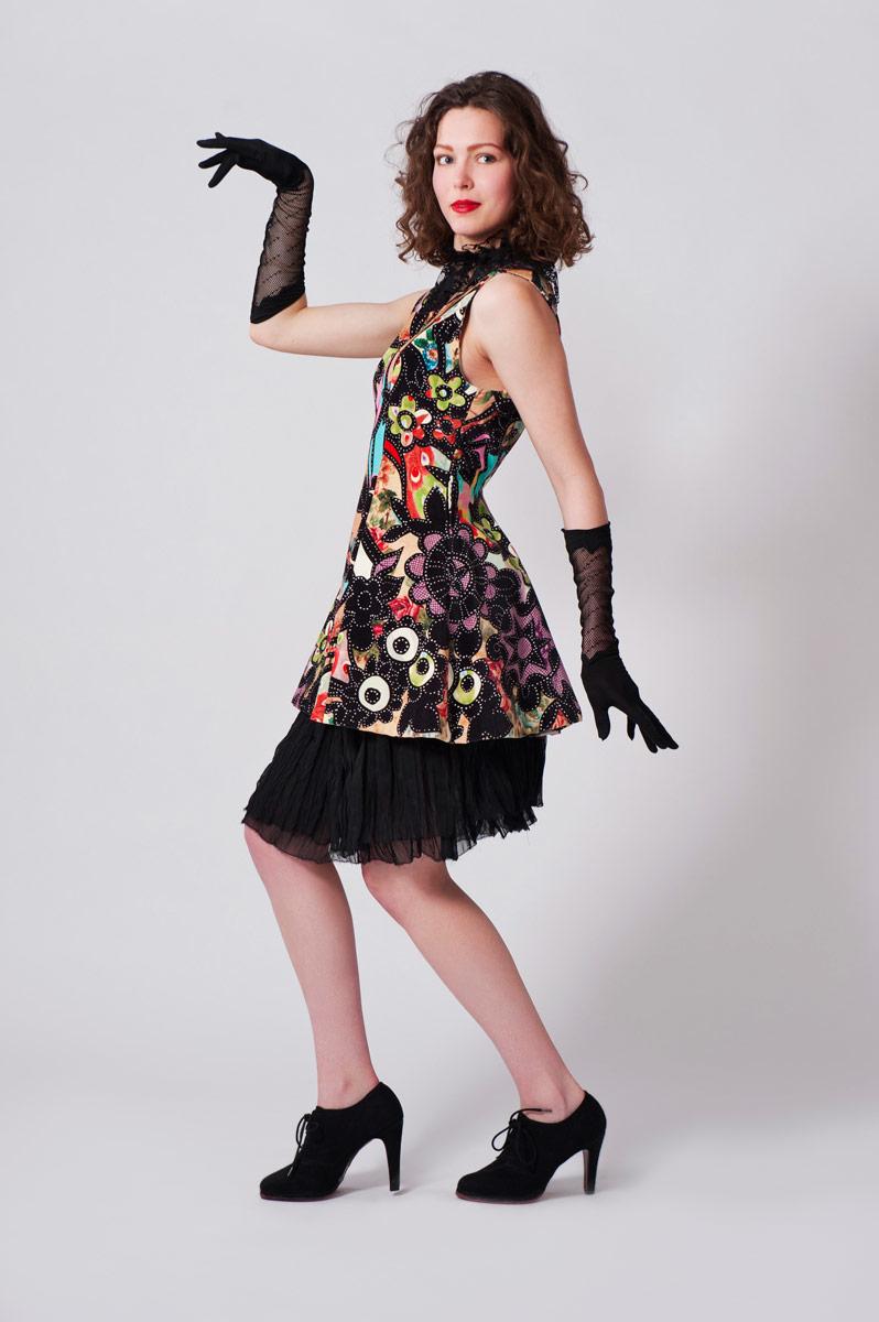 Fluwelen overgooier met bonte print. Zwart rokje van laagjes plissé tule en satijnelastieken band.