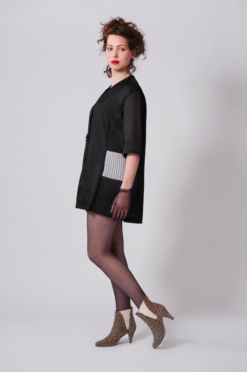 Zwarte blouse van zijde/viscose. Ingelegde stukjes van geplisseerde grijze stof.