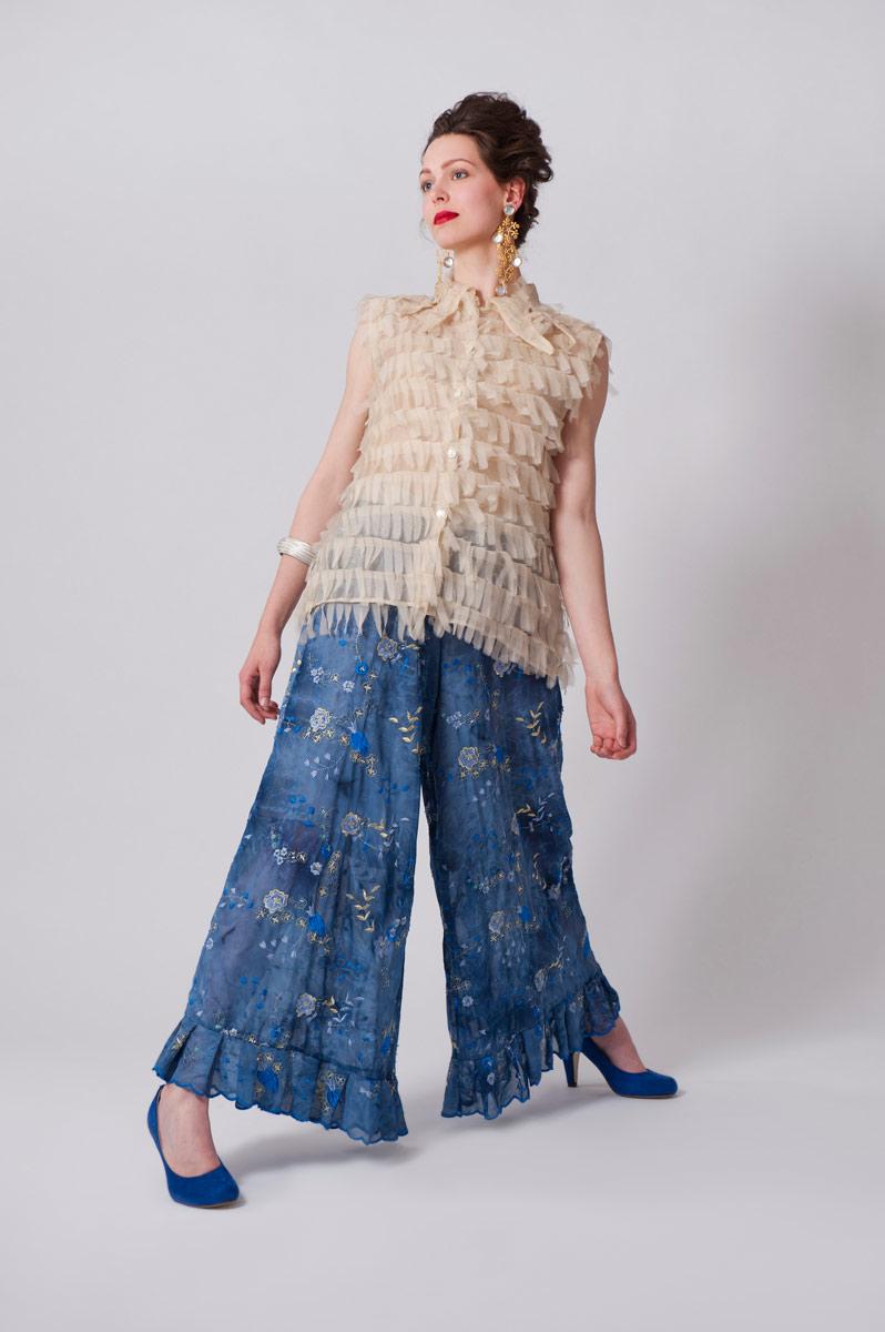 Blauwe wijde gevoerde lange broek van voile stof met glittermotief. Witte zijden blouse van geknipte reepjes.