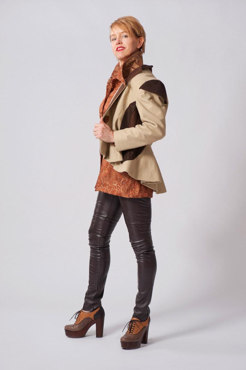 Wollen vilten klokkend jasje in drie kleuren bruin met mouwkappen. Zijden bruine blouse met uitlopende kraag.