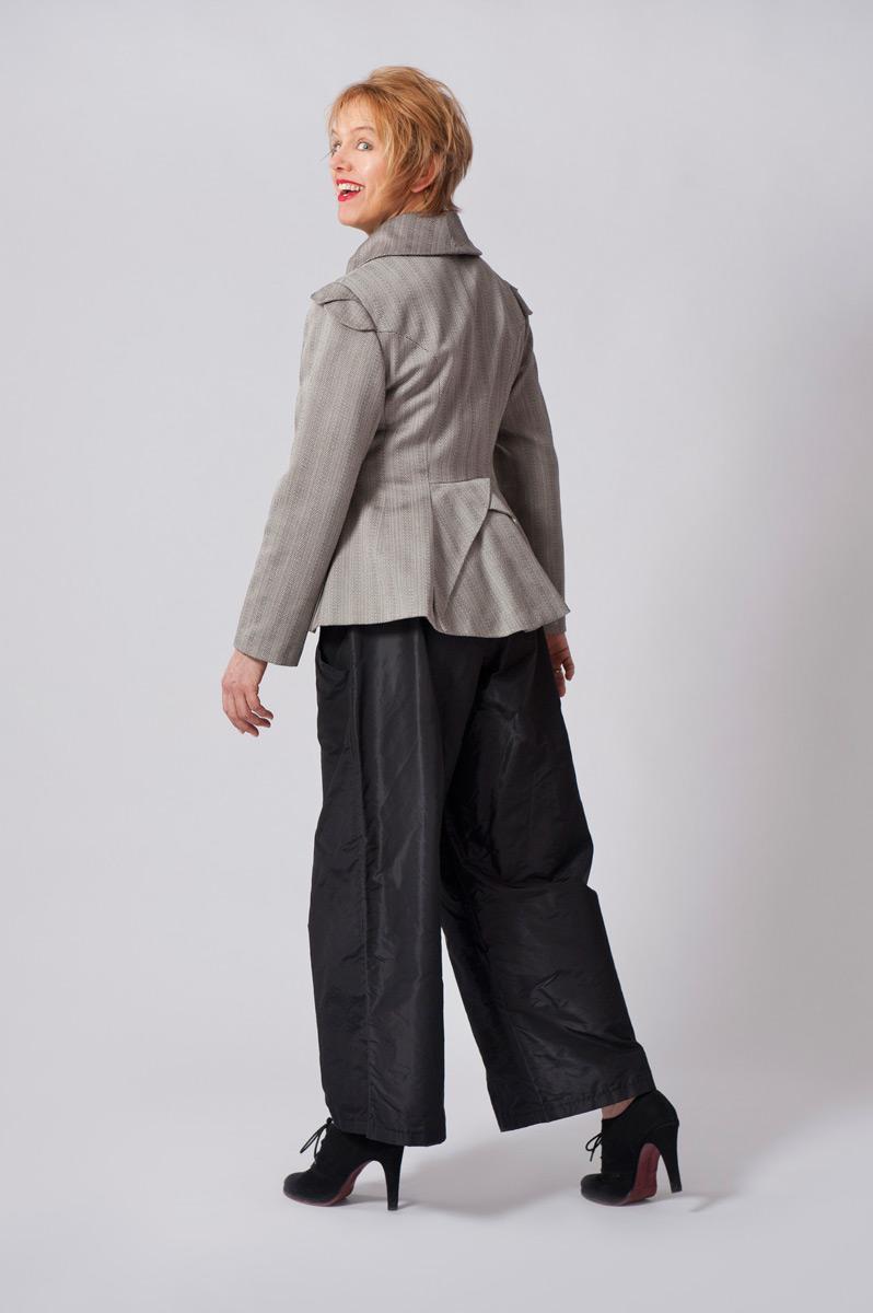 Jasje met visgraatmotief van dunne wollen stof, met dubbele mouwkapjes en overslagen aan de achterzijde.