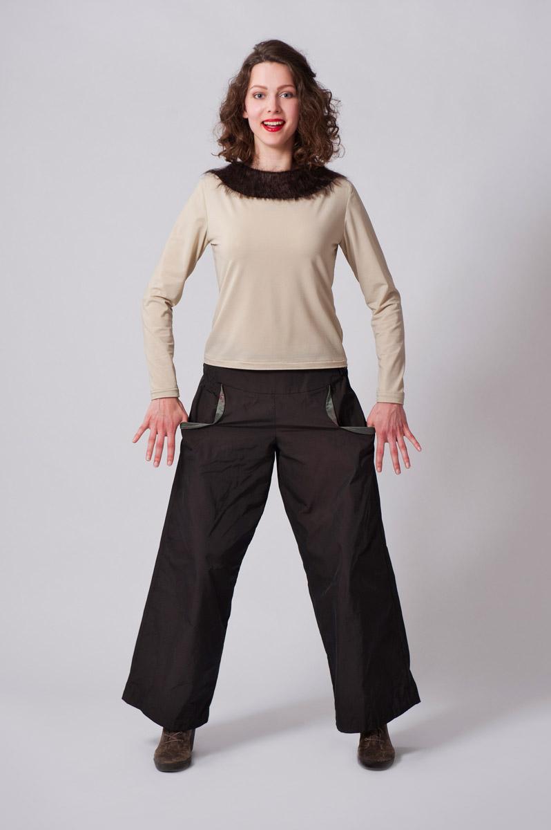 Beige top van synthetisch materiaal met bruine wollen kraag. Bruine wijde lange broek van synthetisch materiaal met ijzerdraad. Zakjes opengewerkt met groene voering.